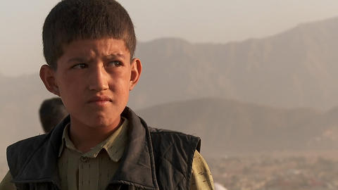 Close up portrait of boy's face as friends fly kites in an empty lot in Kabul, Afghanistan Footage