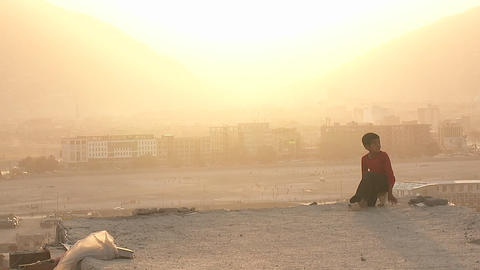 A boy looks out over Kabul Afghanistan during a dust storm Footage