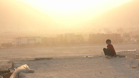 A boy looks out over Kabul Afghanistan during a dust storm Stock Video Footage