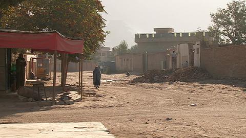 Woman in burqa walks down a street in Kabul, Afghanistan Stock Video Footage