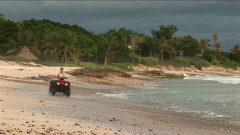 A man rides an ATV through the water on a beach Stock Video Footage