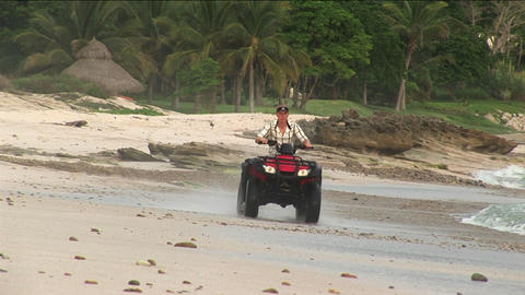 A man rides an ATV through the water on a beach Stock Video Footage
