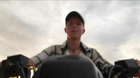 A young man drives an ATV with an overcast sky in the... Stock Video Footage