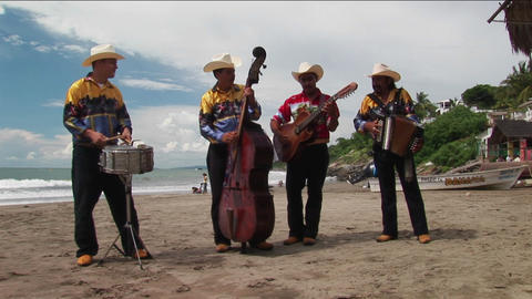 A mariachi band plays on a beach Footage