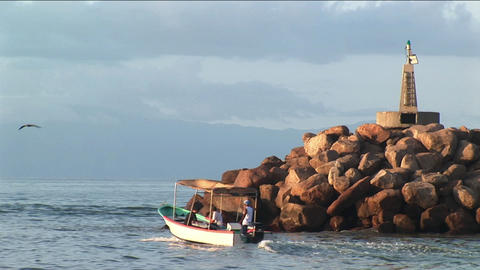 A small power boat cruises past a rocky outcropping in a bay Footage