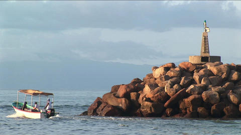 A small power boat cruises past a rocky outcropping in a bay Stock Video Footage