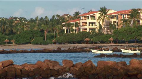 Waves lap against rocky shoreline of beachfront property Footage