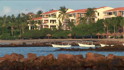 Waves lap against rocky shoreline of beachfront property Stock Video Footage