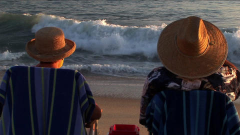 An elderly couple makes a toast to the ocean waves from... Stock Video Footage
