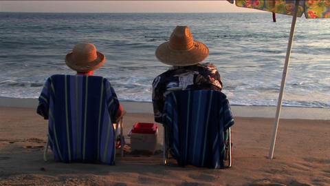 A couple relaxes in beach chairs under an umbrella while... Stock Video Footage