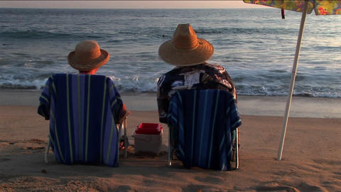 A couple relaxes in beach chairs under an umbrella while watching the ocean Footage
