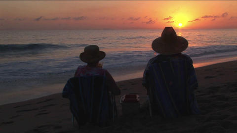 A couple toast the ocean from their chairs on the beach Stock Video Footage