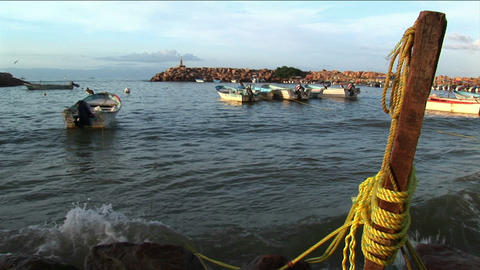 A motor boat tethered to a dock post rocks in the waves Stock Video Footage