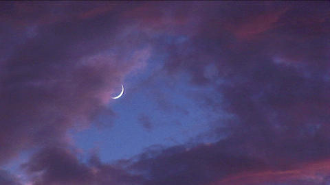Tinted clouds sweep past a crescent moon at golden hour Stock Video Footage