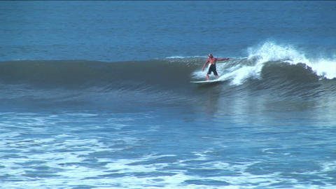 A surfer rides the course of a long surface wave before wiping out Footage