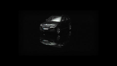 A black BMW SUV spins on display in an all black room Footage