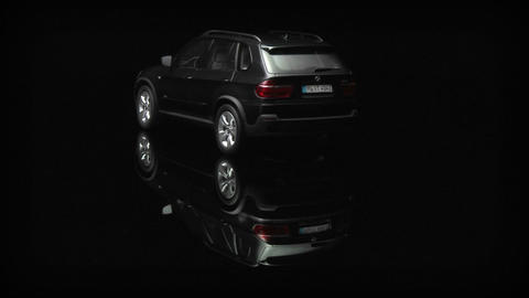A New Four Door Car Is Being Displayed On A Shiny Rotating Surface stock footage