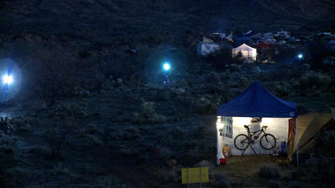 People ride bicycles at night at a campsite Footage