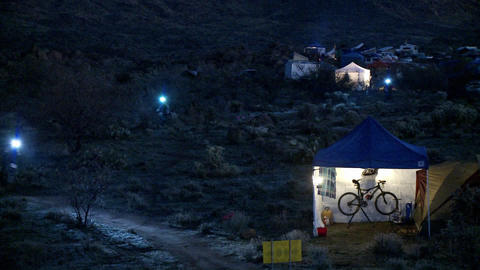 People ride bicycles at night at a campsite Stock Video Footage