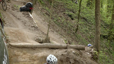 Bicyclists race through a wooded area Footage