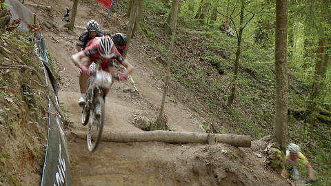 Racing bicyclists jump over an obstacle in the path Stock Video Footage