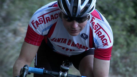 A bicycle racer is coasting along a curve in his route Stock Video Footage