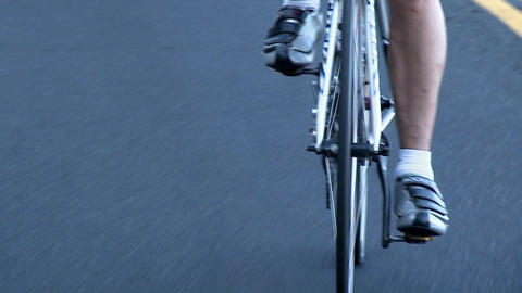 A man rides a bicycle on a stretch of rural highway Stock Video Footage