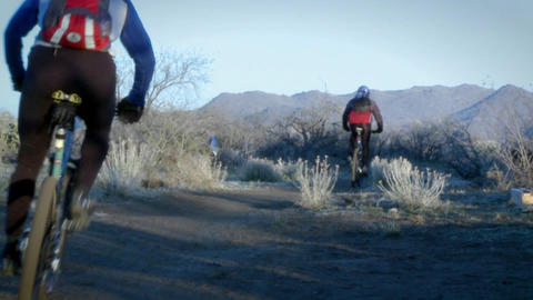 Several bikers ride on a mountain trail Footage