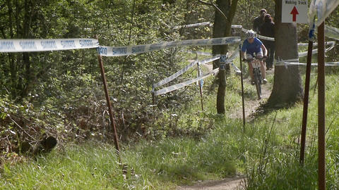 A group of mountain bikers race up a courses trail Stock Video Footage