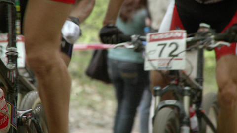 Off road cyclists race up a dirt inclined road Stock Video Footage