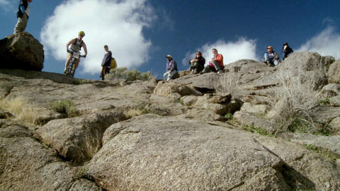 Spectators watch a cyclist ride down a steep rocky trail Stock Video Footage