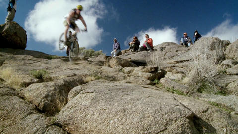 Spectators watch a cyclist ride down a steep rocky trail Footage
