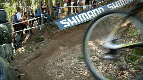 Bicyclists race in the woods as spectators watch Stock Video Footage