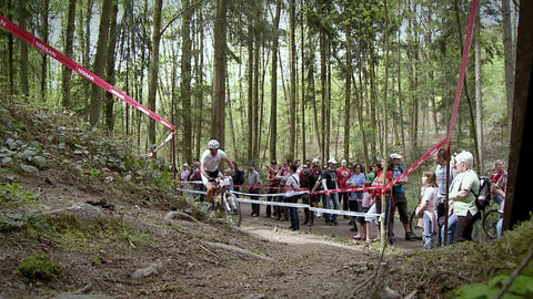 A cyclist races up a rough dirt road course Stock Video Footage