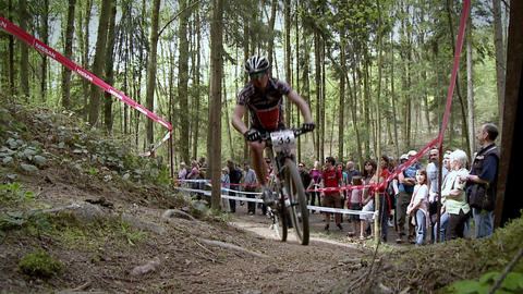 A cyclist races up a rough dirt road course Footage