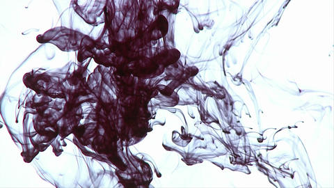 Ink swirls around in various designs after being dropped into a liquid Footage