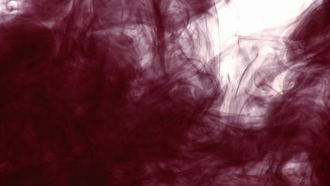 A dark inky substance is dropped into another liquid and makes a swirling design Footage
