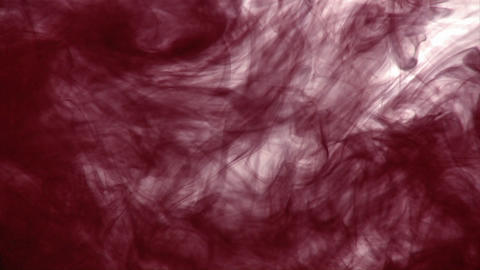 A dark inky substance is dropped into another liquid and... Stock Video Footage