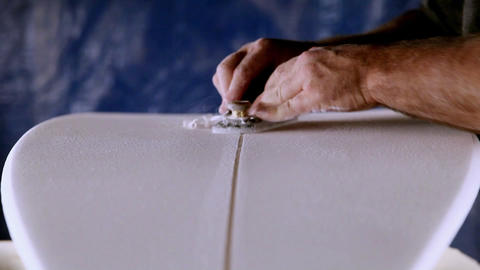 A worker is shaving and cleaning a line through a newly manufactured surfboard Footage