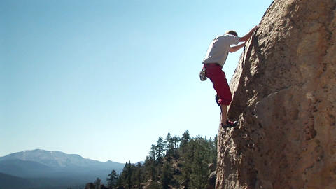 A man climbs up the side of a mountain Footage