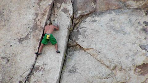 A young man climbs up a mountainside Footage