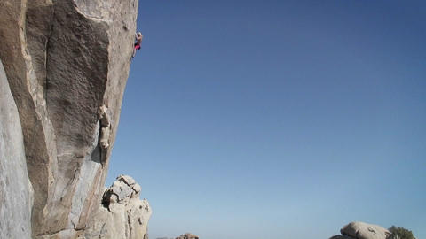 A man climbs the side of a mountain Stock Video Footage