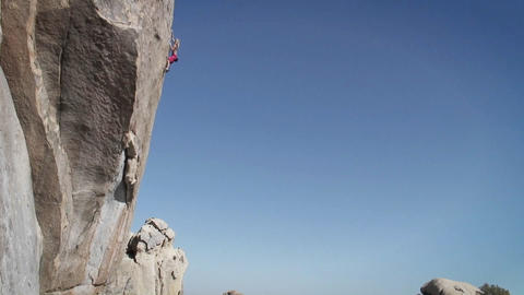 A man climbs the side of a mountain Footage