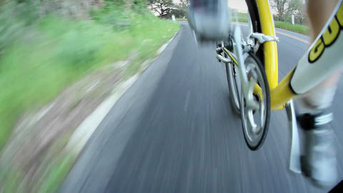 A bicyclist rides down a road Live Action