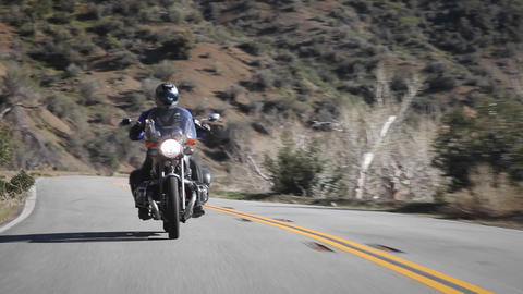 A man rides a motorcycle down a mountain road Footage