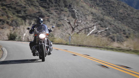 A man rides a motorcycle down a mountain road Stock Video Footage