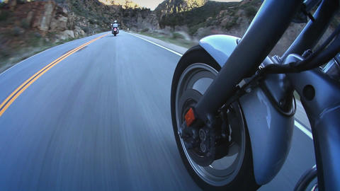 Motorcyclists ride down a mountain highway Footage