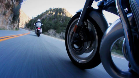 Motorcyclists are riding down a mountain highway Footage
