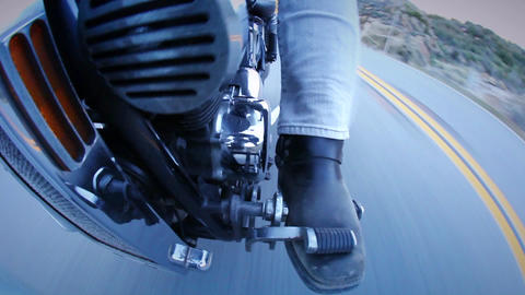 A motorcycle is ridden down a street Footage