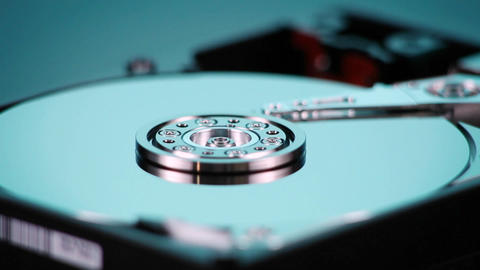 A hard drive with out cover spins slowly on display Footage